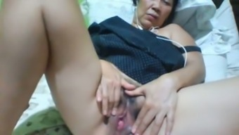 Filipina oily along with dark hair and deflated substantial boobs masturbates herself