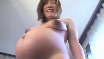 Asian preggo acts with her tits